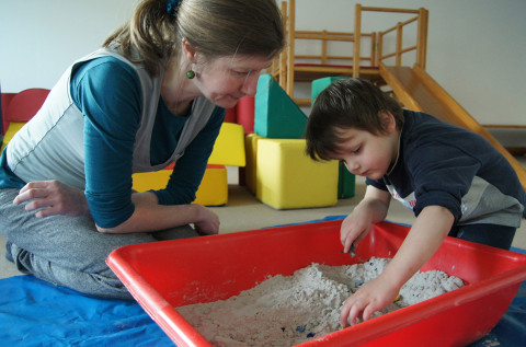 Pädagogin spielt mit Kind in der Sandwanne