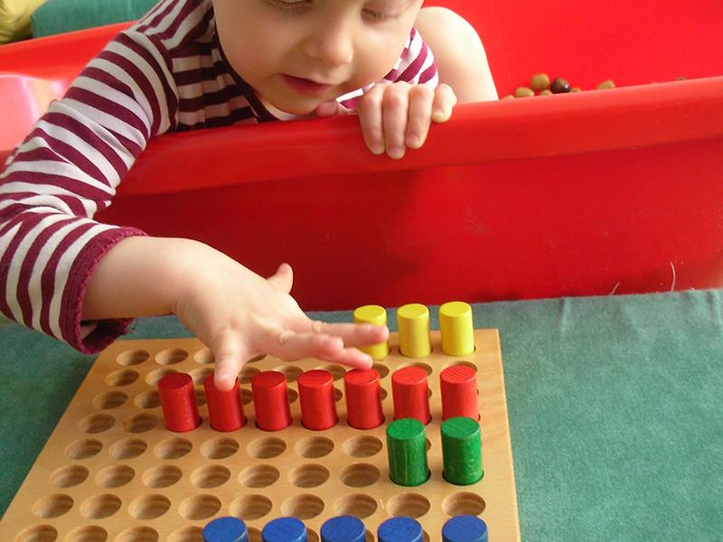 Ein Junge spielt ein Steck-Spiel.